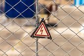 High Voltage Hazard Warning Sign On The Fence. Power Substation With Environmentally Friendly Electr poster