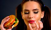 Woman bite big hamburger. Girl eat fast food and lick your fingers after eating. poster