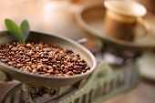 Cup of coffee with beans on old balance scale