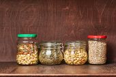 Nuts and seeds in jars in the pantry poster