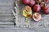 Bottle Of Organic Grape Seed Oil For Spa And Bodycare And Fresh Ripe Grapes Berries On Old Wooden Ta poster