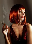 Beautiful woman smoke cigarette, pretty young lady with red hair isolated on dark background, attractive girl in red fashionable dress enjoying cigaret, cute smoker female with luxury hairstyle