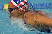 Side view of female athlete swims a breaststroke in pool