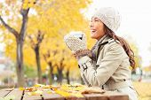 Fall concept - autumn woman drinking coffee on park bench under fall foliage. Beautiful young modern woman smiling happy and cheerful in trench coat.