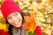 Fall woman looking at copy space holding fall leaves smiling happy and joyful. Lovely beautiful girl