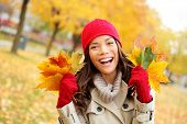 Fall woman happy and bliss in autumn city forest park holding colorful fall leaves smiling happy and