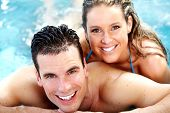 Young happy couple in jacuzzi. Spa relax.