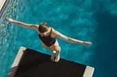 High angle view of a female diver ready to dive while standing at the edge of the springboard