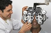 Male optometrist with phoropter while examining patient