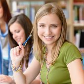 Smiling teenage student girl at study room library high school