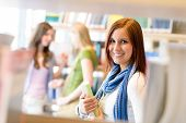 Young student woman choosing book among library shelves