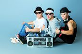 Group of trendy teenagers posing with boombox at studio.