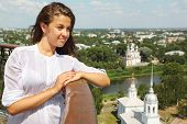 Beautiful girl lean on handrails near Holy Resurrection cathedral in Vologda, Russia