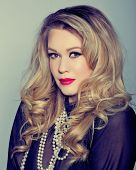 portrait of a beautiful young woman with curly blond hair and glamour make-up with red lips wearing
