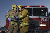 stock photo of fire brigade  - Firefighters reading document with fire truck in the background - JPG