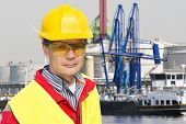 Portrait of a confident docker foreman in front of a petrochemical harbor with gas installations, nu