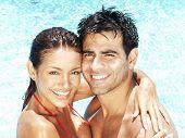 Hispanic young couple enjoying in a swimming pool.