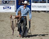 SAN JUAN CAPISTRANO, CA - AUGUST 25: unidentified cowboy carries his saddle in the ring at the PRCA Rancho Mission Viejo rodeo in San Juan Capistrano, CA on August 25, 2012.
