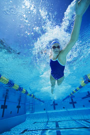 foto of gushing  - Female swimmer gushing through water in pool - JPG