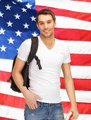 travelling student with backpack and book over american flag