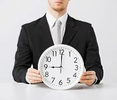close up of man holding wall clock