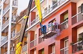 pic of cherry-picker  - Crane working in a red building in Milan - JPG