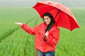 Elated smiling girl during rainy weather outside with umbrella