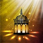 Illuminated intricate Arabic Lamp on shiny abstract background for Ramadan Kareem.