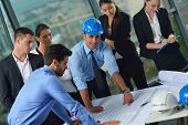 image of blueprints  - business people group on meeting and presentation  in bright modern office with construction engineer architect and worker looking building model and blueprint planbleprint plans - JPG