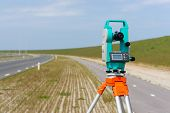 foto of theodolite  - Working with a modern theodolite or total station on a tripod - JPG