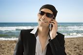 Latin lover calling by phone on the beach