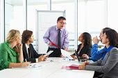 stock photo of conduction  - Businessman Conducting Meeting In Boardroom - JPG