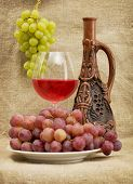 picture of loamy  - Ceramic brown bottle grapes and red wine on canvas