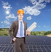 Architect wearing helmet and holding blueprints, with solar photovoltaic cell panels in the backgrou