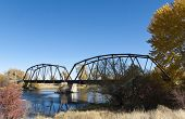 picture of trestle bridge  - A trestle bridge spans a river in the Fall season - JPG