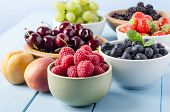 picture of fruit  - A selection of different Summer fruits in a variety of bowls on a painted blue wood planked farmhouse kitchen table against a light blue background.