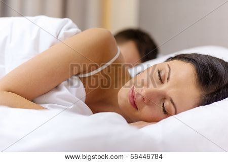 hotel, travel, relationships, and happiness concept - happy couple sleeping in bed poster