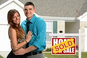 Young couple in front of newly purchased home