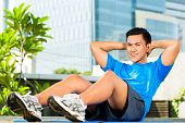 Urban sports - young Asian Indonesian man is doing warming up and sit-ups before running in the city