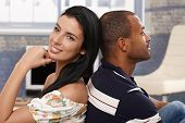 Happy interracial loving couple sitting at home back-to-back, smiling.