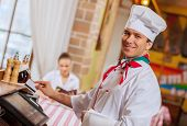 Image of handsome chef inserting card in terminal