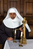 Nun standing at the altar and lighting a candle