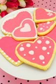stock photo of poka dot  - Plate of heart shaped cookies with pink frosting and pink pattered background - JPG
