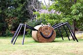 Huge spider made from pipes and round bail of hay, decoration for Halloween