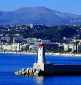 Lighthouse in the bay of the city on a background of mountains