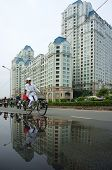 People Ride Bicycle With High-rise Building Background