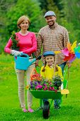 Gardening, planting - happy family with wheelbarrow working in the garden