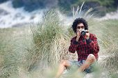 Hipster man taking photos with toy camera at the beach