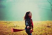 stock photo of ordinary woman  - young happy woman run in park misty winter day retro colors - JPG