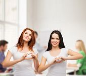 friendship, education and happy people concept - two smiling girls in white t-shirts showing heart with hands